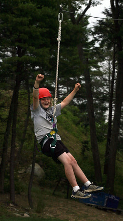 Manchester: Ian Prince, 9, of Gloucester cheers as he uses the new zip line at the Manchester Athletic Club during Blue Sky Adventure Camp. Prince says the only scary part is climbing up to the platform and looking down, but loves feeling like he's flying. Photo by Kate Glass/Gloucester Daily Times