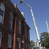 David Le/Gloucester Daily Times. Gloucester DPW masons were lifted high up onto the roof of town hall on Friday morning to dismantle two chimneys that were ordered to be taken down before the hurricane. 8/26/11.