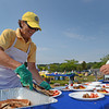 Gloucester: Terri Jones places some blueberry Pancakes on a plate, as the new president of the Rotary Uncle Tony does the sauages and fruits at the Rotary Pancake Breakfast at Stage Fort Park Saturday morning.Desi Smith /Gloucester Daily Times. August 20,2011