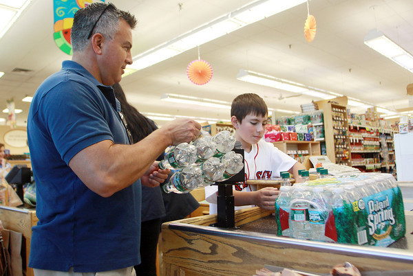 David Le/Gloucester Daily Times. Chris Colocousis and his son Nik, 12, of Manchester buy some cases of water at Crosby's Marketplace in Manchester on Friday afternoon. 8/26/11.