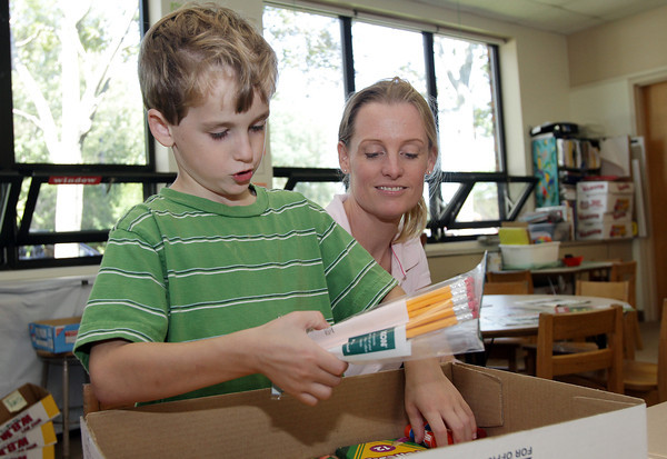 Cathy Kelley, of Rockport, watches as her son, Colin, 7, looks through a box of new school supplies at his desk in his new first grade classroom on Monday afternoon. David Le/Gloucester Daily Times.