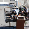 David Le/Gloucester Daily Times. Gloucester DPW masons Joe Silva, left, and Scott Amero, right, work to take apart one of two chimney's on the roof of town hall that were ordered to be taken down in preparation for Hurricane Irene. 8/26/11.