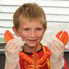 Rockport: Kyle Marek 8, holds up one of the many lobsters he help serve at Lobster Fest Saturday afternoon. Kyle is also the president of the Kids Rotary Club at the Rockport Elementry School. Desi Smith/Gloucester Daily Times. August 13, 2011