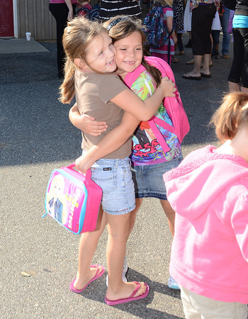 Gloucester: Morgan Penniompede 5, hugs her friend Cameron Carroll 5,goodbye on her first day as a kindergartener at the Verterns Memorial School on Webster St. Morgan will start her school year tomorrow. Desi Smith /Gloucester Daily Times. August 31,2011