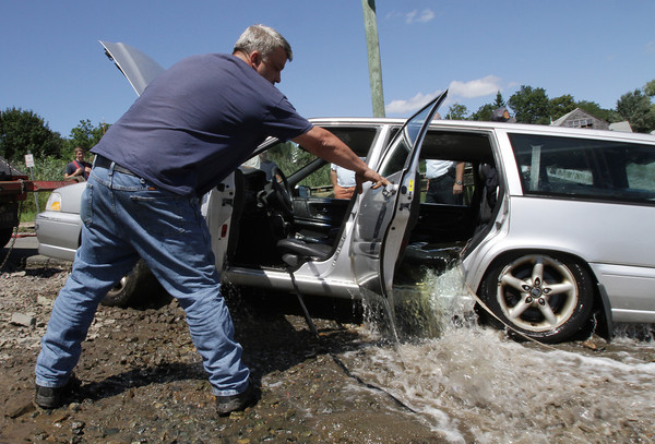 David Le/Gloucester Daily Times. Scott Sholds, of Tally's Truck Center and Towing Service opens the back door of a Volvo station wagon to let out water after it had rolled into the Essex River on Monday afternoon. 8/22/11.