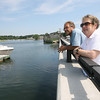 Bob Coviello and Sue Lufkin of Essex look out over the Essex River at the site of a proposed boardwalk, which would run along the Causeway and provide additional space for boaters visiting businesses downtown. Photo by Kate Glass/Gloucester Daily Times