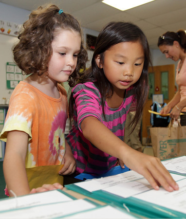 Shayla Schafer, 7, right, a second grader at the Rockport Elementary School helps first grader Sophia Sekercan, 6, get acclimated with her new classroom on an Open House on Monday in preparation for school opening on Tuesday. David Le/Gloucester Daily Times.