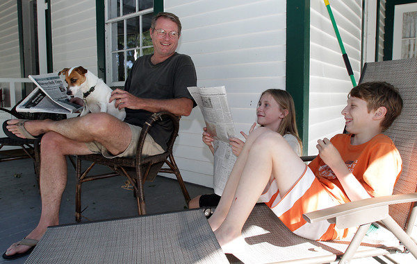 Gill Deford, left, sits with his son Jack, 11, right and their neighbor Emilee McDonald, 12, on their porch as they waited for workers to try and restore power on Tuesday afternoon. David Le/Gloucester Daily Times