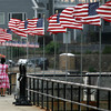 David Le/Gloucester Daily Times. A woman walks her dog along Stacy Boulevard as a strong wind whips through the American flags that line the walkway by the ocean. 8/19/11.