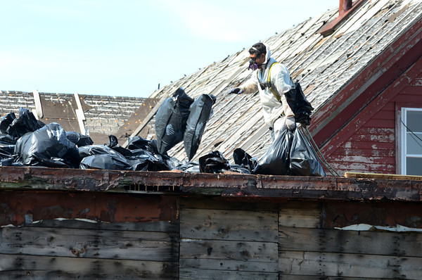 Gloucester: A worker from Air Quality Experts Inc, remove bags of hazardous waste fom the roof of the Paint Factory Wednesday morning. A section of the building is scheduled for demolition tomorrow. Desi Smith /Gloucester Daily Times. August 28,2011