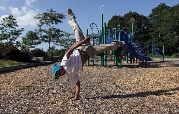 David Le/Gloucester Daily Times. Takashi Pin, 15, of Lowell, does a 1-armed flip at Stage Fort Park in Gloucester on Friday afternoon. 8/26/11.