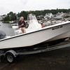 David Le/Gloucester Daily Times. Mark McManus, of Essex, sits in his boat as it gets towed out of the water by his brother Tim McManus, of Beverly, in preparation for Hurricane Irene. 8/25/11.