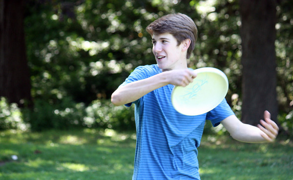 Sam Cunningham of Gloucester throws around the frisbee with his friends William Gleckner and Dan DeMarco of Rockport at Millbrook Meadow.  Photo by Maria Uminski/Gloucester Daily Times