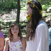 "David Le/Gloucester Daily Times. Maggie Clary, 10, left, looks up at Tori Hilshey, 18, as she holds a flower in her mouth and wears a wreath of flowers in her hair to celebrate ""Decades Week"" at the Cape Ann YMCA on Thursday. 8/19/11."