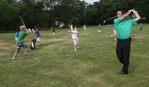 Josh Durick demonstrates how to follow through on a swing during the Bass Rocks Junior Clinic at the Bass Rocks Golf Club yesterday morning.  Photo by Kate Glass/Gloucester Daily Times