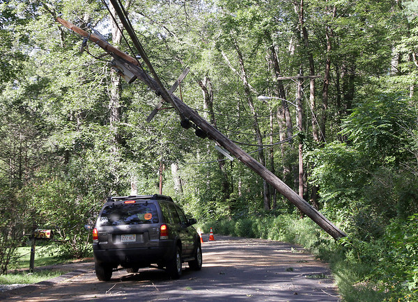 A car drove underneath a telephone pole even though it was hanging precariously by its wires above a debris strewn road, on Sumner St. in Gloucester on Monday afternoon. David Le/Gloucester Daily Times.