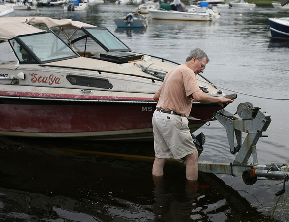 David Le/Gloucester Daily Times. Brian Miller, of Manchester, tightly secures his boat to the trailer before towing his boat out of Manchester Harbor on Thursday afternoon in preparation for Hurricane Irene. 8/25/11.