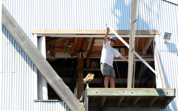 David Le/Gloucester Daily Times. Tim Macort, a worker at Crocker's Boat Yard in Manchester, helps guide a mast into storage on Friday afternoon. Many people opted to take their boats out of the water in anticipation of the upcoming hurricane. 8/26/11.