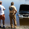 David Le/Gloucester Daily Times. Two men gaze out at a silver Volvo which had rolled into the Essex River on Monday afternoon while a boat was being put in the water. 8/22/11.