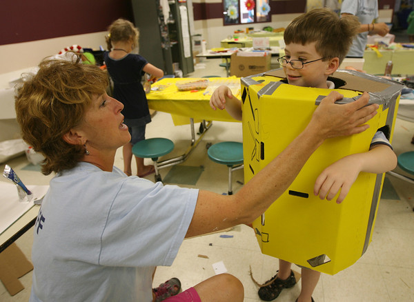 Tina Lamond helps Damian Sorrenti fit into a robot body that he made during the Rockport Recreation Department's Summer Fun program at the elementary school yesterday morning. Photo by Kate Glass/Gloucester Daily Times