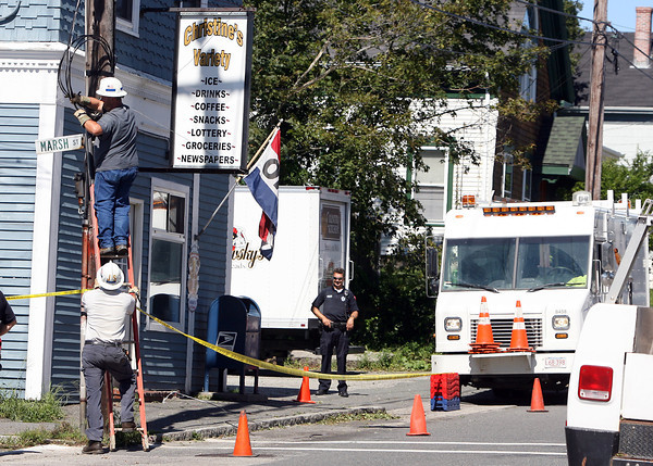 A couple National Grid employees work to tie up an electrical wire that was taken down by a falling tree branch in front of Christine's Variety Store on the corner of Marsh and Washington Streets. David Le/Gloucester Daily Times.