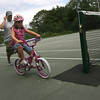 Manchester: Manuel Carvalho runs alongside his daughter, Ceece Carvalho, 6, as she rides her bike around the tennis courts at Coach Ed Field Playground. It is Ceece's first summer riding her bike without training wheels. Photo by Kate Glass/Gloucester Daily Times