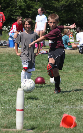 Nicholas Costa and Dillon Vanderpool take turns trying to knock over a candlepin during North Shore United's Soccer Clinic at Magnolia Woods yesterday. Photo by Kate Glass/Gloucester Daily Times