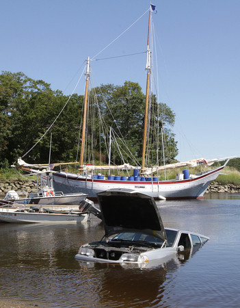 David Le/Gloucester Daily Times. A half-sunk Volvo station wagon sits in the Essex River waiting to be pulled out, as the Schooner Ardelle sits in the background, awaiting a stabilization test from the Coast Guard. 8/22/11.