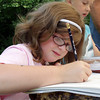 David Le/Gloucester Daily Times. Chanel Richards, 7, concentrates as she draws a portrait during Tedy D'Agostino's free art workshop called Kids Korner, held at his studio in Rockport. 8/25/11.