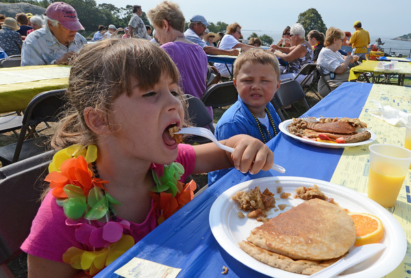 Gloucester: Aria Caputo 6, enjoys her pancake breakfast as her brother Jack looks on at the Rotary Pancake Breakfast at Stage Fort Park Saturday morning.Desi Smith /Gloucester Daily Times. August 20,2011
