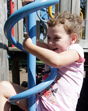 David Le/Gloucester Daily Times. Ava Rizzico, 5, of Manchester, hangs onto a spiral pole as she slides down it at Masconomo Park on Wednesday. 8/17/11.