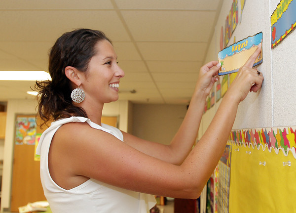 Jaclyn Baldassano, a Kindergarten teacher at Beeman Memorial hangs up birthday months on the wall in her classroom on Tuesday. David Le/Gloucester Daily Times
