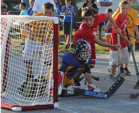 Steven Tettoni of the Red Wings scores against the Bruins during a Young Legends Street Hockey tournament game at Stage Fort Park. Photo by Maria Uminski/Gloucester Daily Times