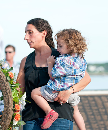 Gloucester: Josie Russo who lost her husband and father on board the Patriot while pregnant, lays a wreath at the Fishermen's Memorial with her son (not born at the time) at a memorial service held Saturday afternoon at the Fishermen's Statue. Desi Smith/Gloucester Daily Times. August 13,2011