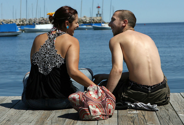 David Le/Gloucester Daily Times. Danielle Guarracino, left, and Jake LoPresti, sit and enjoy the warm August sunshine on a dock in Rockport Harbor. 8/23/11.