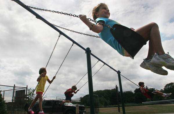 Six year old triplets Ellie, Lucy and Max Wendell along with their 8 year old brother James, all of Ipswich, enjoy their time on the swings at Memorial Field playground in Essex.