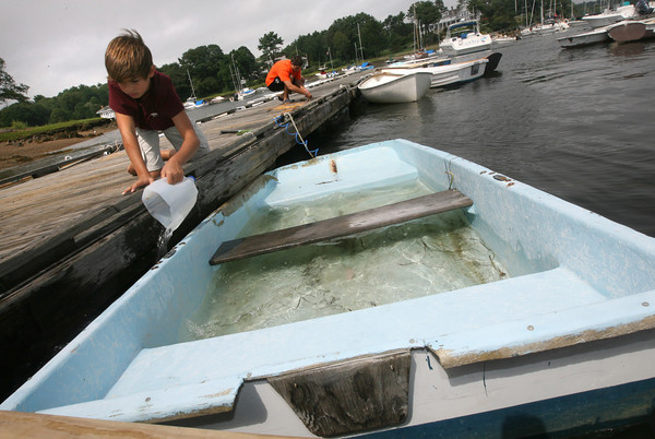 Manchester: Benji Daniels, 11, bails out a boat at Tuck's Point yesterday afternoon. He saw a lot of water in the boat and even though it wasn't his, wanted to lend a helping hand. Photo by Kate Glass/Gloucester Daily Times