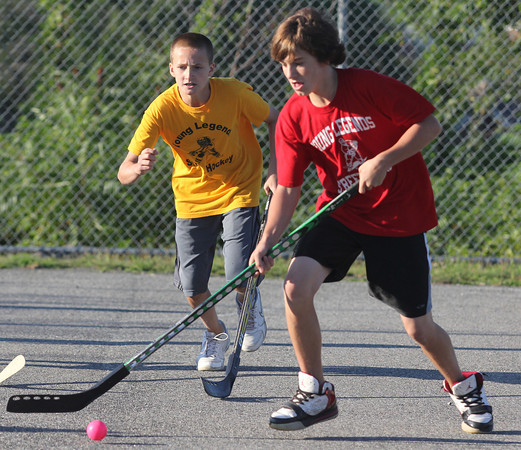 Joey Ogonowski of the Bruins and Terrance Lane of the Red Wings battle for the ball during a Young Legends Street Hockey tounament game at Stage Fort Park. Photo by Maria Uminski/Gloucester Daily Times