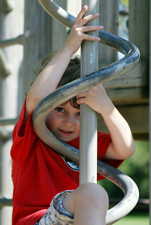 David Le/Gloucester Daily Times. Sammy Rizzico, 4, of Manchester, peers through the bars as he slides down a spiral playground pole at Masconomo Park on a warm August afternoon. 8/17/11.