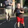 Zachary Zindle, 5, of Gloucester, laughs as he beats his father John, in a race around the Gloucester High School track. David Le/Gloucester Daily Times