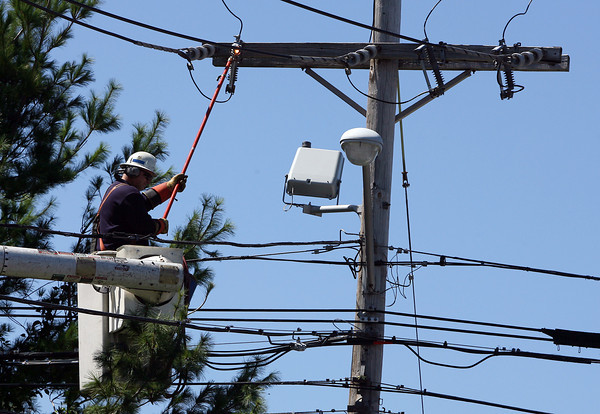 A National Grid worker uses an extension tool to try and fix a connection on top of a telephone pole on Eastern Ave. on Monday morning in the wake of Hurricane Irene. David Le/Gloucester Daily Times.