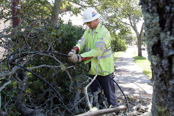 National Grid employee Jonathan Strong works to cut away an electrical wire from a tree branch that had fallen into the road near Christina's Variety Store at the corner of Marsh and Washington Streets. David Le/Gloucester Daily Times.