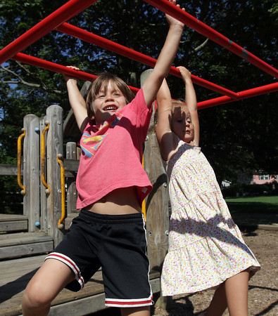 David Le/Gloucester Daily Times. Sebastian Spinelli, 6, left and his sister Alexia, 4, swing together on the monkey bars at Masconomo Park in Manchester on Wednesday afternoon. 8/17/11.