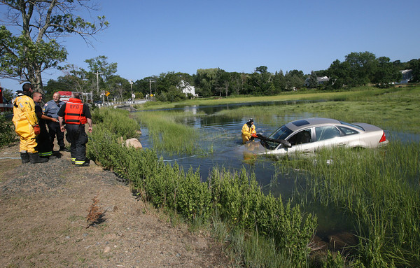 Essex Firefighter Warren Grant prepares a car to be towed by Tally's after it rolled from the Farnham's parking lot and into the water across the street. Photo by Kate Glass/Gloucester Daily Times