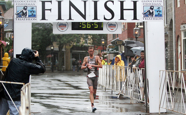 David Le/Gloucester Daily Times. On a rain-soaked Sunday morning, Ethan Brown crosses the finish line for the Gloucester Fisherman Triathlon on Main St. completing the course in 56:51. 8/7/11.