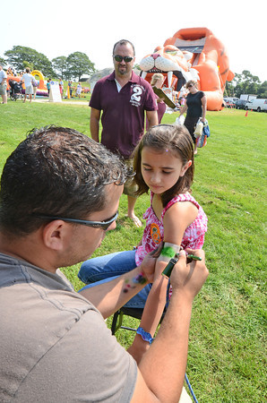 Gloucester: Brian Raney of Beach Front Body Art in Manchester NH. sprays a temporary tattoo of a turtle on the arm of Rylea Bogacz 8, of Attleboro,Ma while dad Joe looks on,Saturday afternoon at the Waterfront Festival held at Stage Fort Park.  Desi Smith /Gloucester Daily Times. August 20,2011