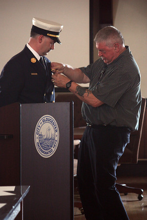 MARIA UMINSKI/Gloucester Daily Times. After being sworn in as Gloucester's new fire chief, Eric Smith recieved a pin from his father, Ralph Smith, at the Public Safety Badge Ceremony at Gloucester Town Hall.