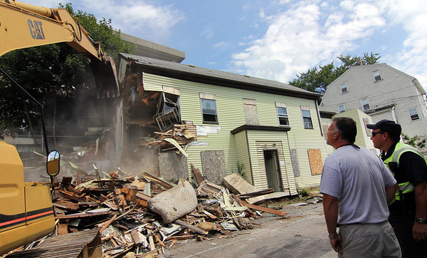 ALLEGRA BOVERMAN/Staff photo. Gloucester Daily Times.  Local contractor Gary Thornton, left, and Gloucester police officer Kevin Mackey, right, watch the demolition of 12 Columbia Street in Thursday morning.