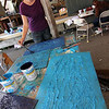 "ALLEGRA BOVERMAN/Gloucester Daily Times.  Lanesville artist Camilla MacFadyen held a two-day workshop at Maritime Gloucester about collograph printmaking. Students collected seaweed at the pier in back of the museum, made plates by gluing the seaweed to cardboard pieces, like the one shown here, and being worked on by participant Alice Morris, and applied fabric paint to the three-dimensional surface to print onto dozens of yards of silk chiffon and organza to make a collaborative art installation piece for the museum. The museum also provided fish to create prints from onto fabric and stuffed fish were sewed to swim in the silky virtual aquarium of seaweed images. A ""Stock the Tank"" party that highlighted the group art piece was held on August 18, and the installation will be on view for the rest of the month at Maritime Gloucester. See their website for museum hours at <a href=""http://maritimegloucester.org/"">http://maritimegloucester.org/</a>"