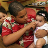 ALLEGRA BOVERMAN/Staff photo. Gloucester Daily Times. Gloucester: Emanuel Tejada, 12, center, of Gloucester, cuddles his new baby sister, Ashlenny Tejada, four months old, while his little brother Miguel, 2, left, eats his lunch. They and two other sisters and their mother were having lunch, playing games and harvesting in the garden at The Open Door on Thursday.